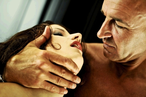 Shaved head man clasping the throat of dark haired woman
