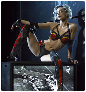 pole dancer Felix Cane sitting on a tv for her routine in Zumanity