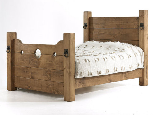 a craftsman style wooden bed with the footboard fashioned in the style of punishment stock or pillory