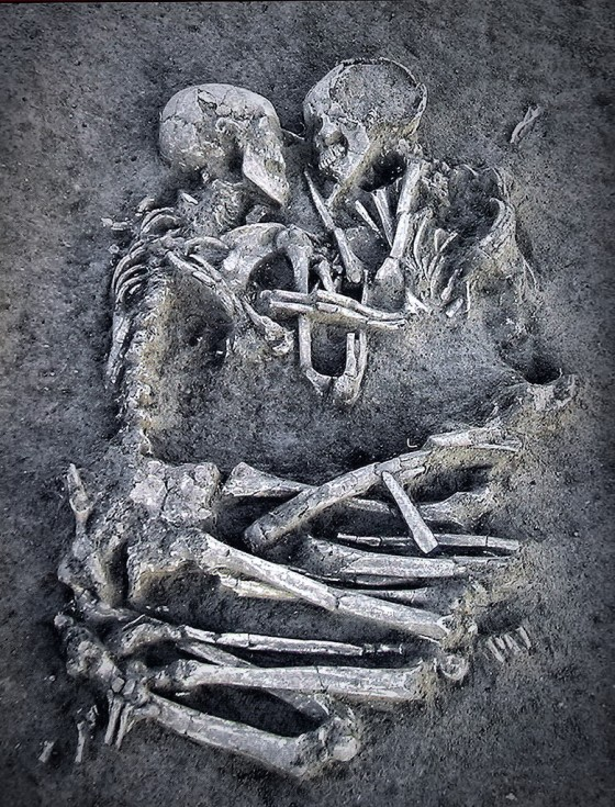 two skeletons of a couple entombed clasping each other