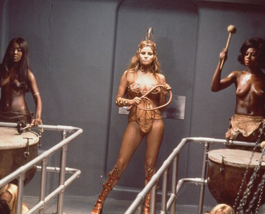 Raquel Welch in her whip cracking barbarian outfit with two topless drummers in the slave rowing galley