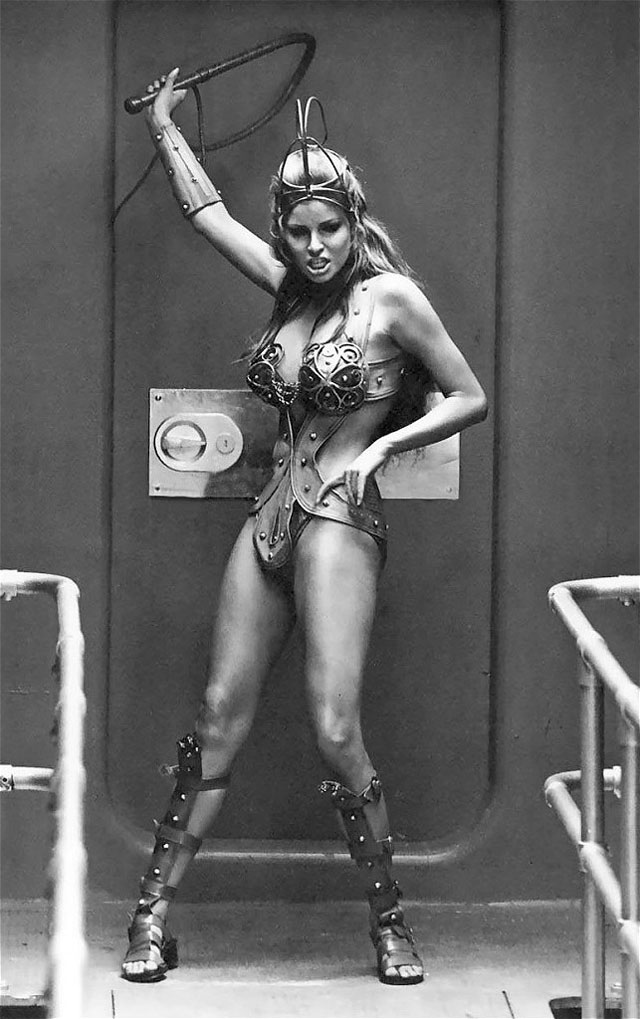 Raquel Welch cracking the whip at the rowing galley slaves in the movie The Magic Christian
