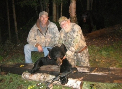 two hunters gloating over a dead black bear while a live one approaches from the rear