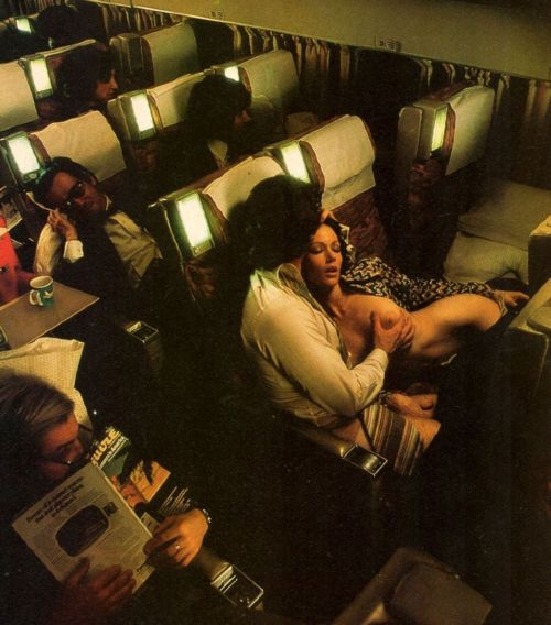 a man a woman getting intimate in an airplane cabin