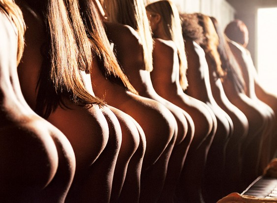 a rear view of a row of nude women focused on their highlighted backs and asses