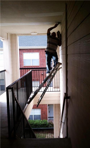humorous image of man precariously positioned on a ladder