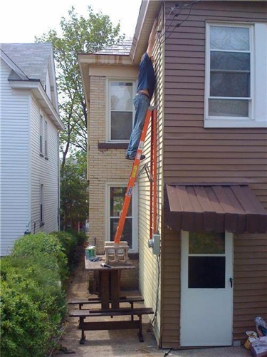 man dangerously using a ladder